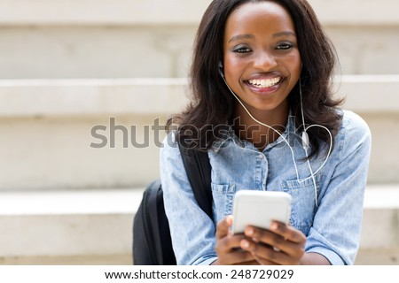 portrait of young african american college student with smart phone - stock photo