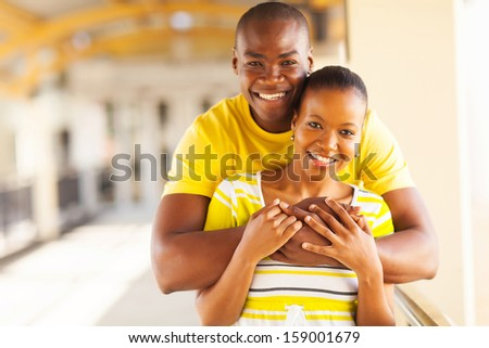 portrait of young african american couple hugging - stock photo