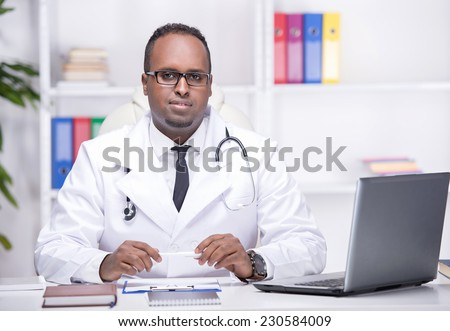 Portrait of young African American doctor is sitting in his office and looking at the camera.