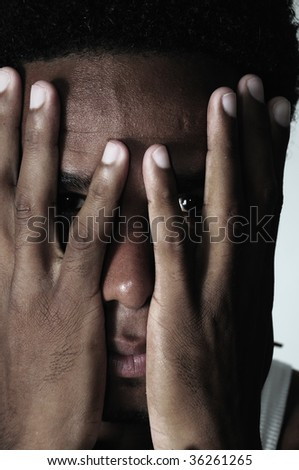 Portrait of young african american frustrated man with hands on the face - stock photo