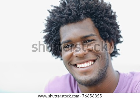 portrait of young african american guy looking at camera near the sea. Horizontal shape, head and shoulders, copy space - stock photo