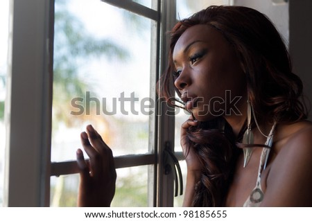 Portrait of young african american looking through a window. - stock photo