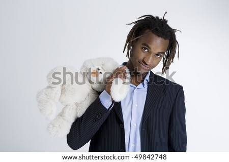 Portrait of young African American man holding teddy bear, studio shot - stock photo