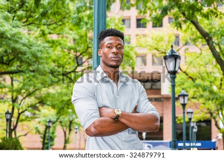 Portrait of Young African American Man. Wearing gray shirt, rolling over sleeves, jeans, wristwatch, crossing arms, a black guy standing against light pole on street in New York, waiting for you.  - stock photo