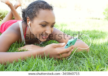 Portrait of young african american teenager girl using smartphone and headphones to listen to music, smiling laying on grass park, outdoors. Adolescent technology lifestyle, sunny exterior, holiday. - stock photo