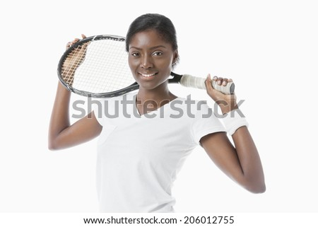 Portrait of young African American woman holding racket over white background - stock photo