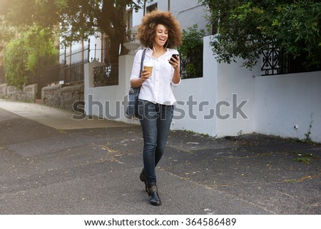 Portrait of young african american woman walking and looking at cellphone - stock photo