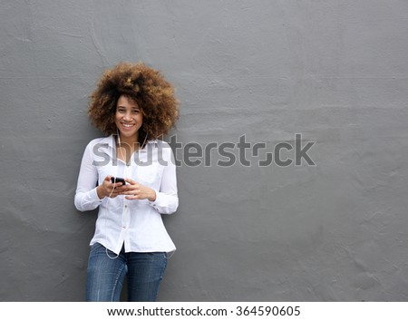 Portrait of young african american woman with afro listening to music on smart phone - stock photo
