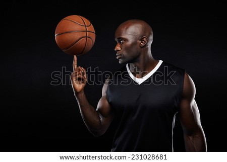 Portrait of young african athlete balancing basketball on his finger against black background. Focused basketball player. - stock photo
