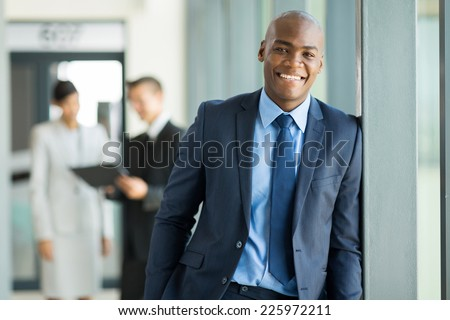 portrait of young african businessman with colleagues on background - stock photo