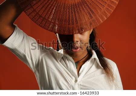 Portrait of young african fashion female covering face with a fan - stock photo
