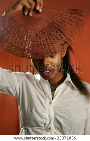 Portrait of young african female model holding fan - stock photo
