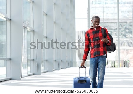 Portrait of young african guy walking with suitcase and looking at mobile phone at airport