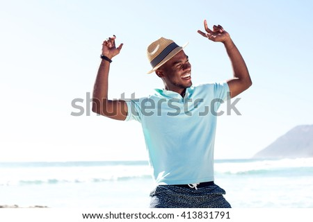 Portrait of young african man having fun at the beach on summer day - stock photo