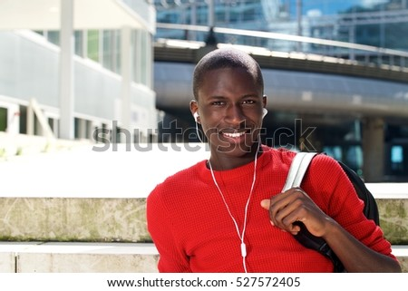 Portrait of young african man sitting outdoors with earphones and bag
