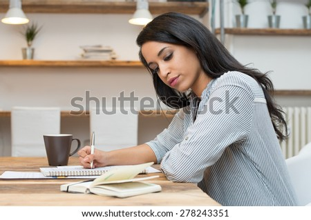 Portrait of young african woman studying at the library - stock photo