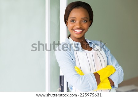 portrait of young african woman wearing apron at home - stock photo