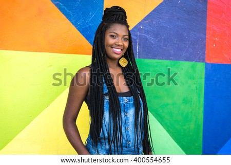 Portrait of Young Afro Brazilian woman smiling on colorful background - stock photo