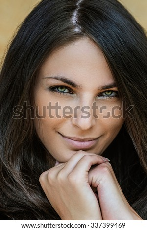 Portrait of young alluring smiling attractive brunette woman propping up her face against yellow background.