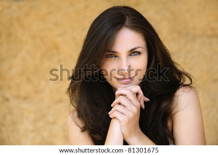 Portrait of young alluring smiling attractive brunnete woman propping up her face against yellow background. - stock photo