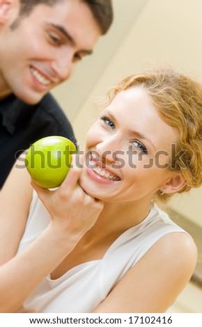 Portrait of young amorous couple with apple at home - stock photo
