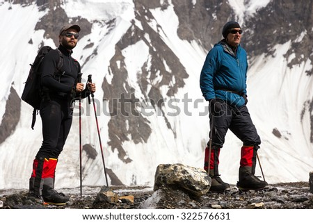 Portrait of Young and Aged Climbers Two Athletes in High Altitude Alpine Boots Gear and Clothing Staying on Glacier and Looking Snow and Ice Steep Slope on Background - stock photo