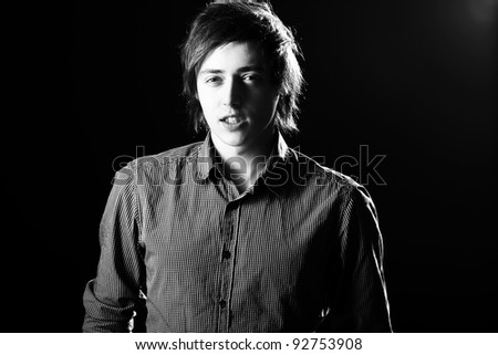 Portrait of young and attractive guy over black background - stock photo