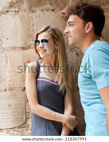 Portrait of young and attractive romantic tourist couple enjoying a day out together sightseeing, smiling against an old stone wall in a destination city, outdoors. Romantic travel and relationships. - stock photo