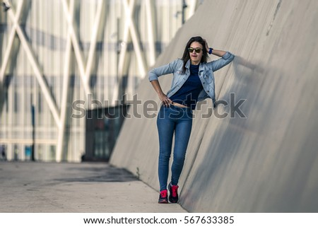 Portrait of young and attractive woman standing next to the wall in industrial park on cloudy day, Port Forum, Barcelona, Spain.