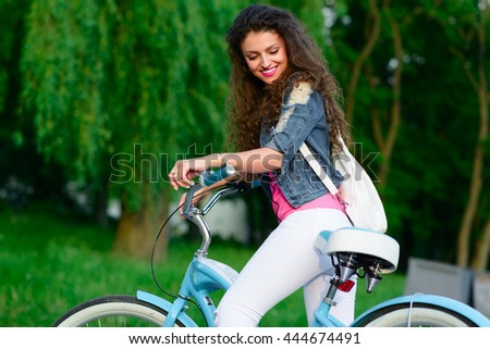 Portrait of young and beautiful girl with curly hair riding on a bicycle in the park in the summer in the city. Outdoor portrait