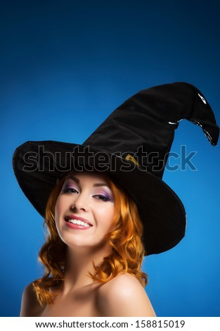 Portrait of young and beautiful witch over blue background
