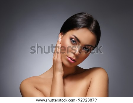Portrait of young and beautiful woman over grey - stock photo