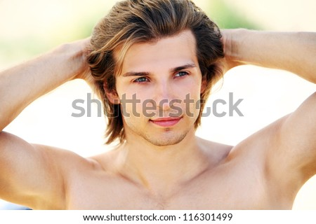 Portrait of young and handsome guy with long hair on the beach - stock photo