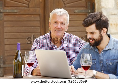 Portrait of young and senior winery owners working together. Old winemaker and smiling sommelier working with laptop while tasting wines. Small business.