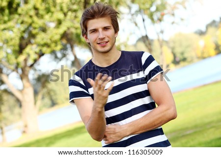 Portrait of young and smiling cute man in park - stock photo