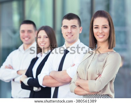 Portrait of young and successful businesswoman with her arms crossed portrayed together with her colleagues - stock photo