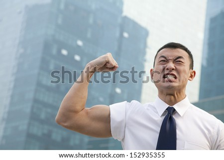 Portrait of young angry businessman flexing muscles - stock photo