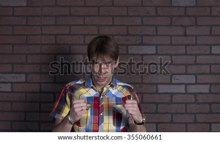 Portrait of young angry man. Brick wall background - stock photo