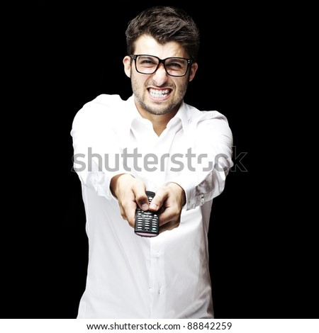portrait of young angry man holding control tv over black background - stock photo