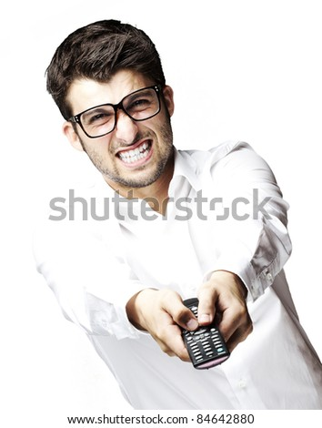 portrait of young angry man holding control tv over white background - stock photo