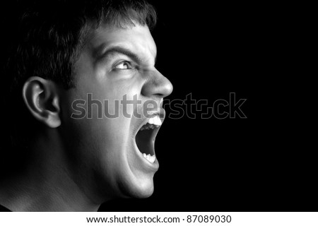 portrait of young angry man screaming isolated on black background with copyspace - stock photo