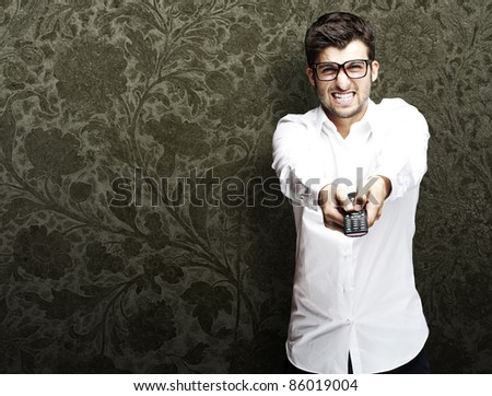 portrait of young angry man using remote control against a vintage background - stock photo