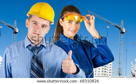 Portrait of young architects at in front of construction site, building and crane. - stock photo