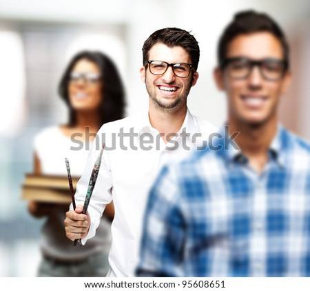 portrait of young art students holding books indoor - stock photo