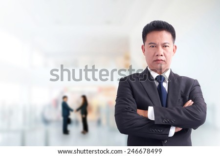 Portrait of young asia businessman has office background .cross one's arm,Positive emotion - stock photo
