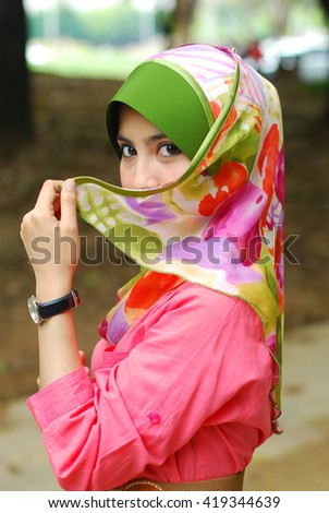 Portrait of young asian beautiful muslim woman in hijab with covered face looking to the camera - stock photo