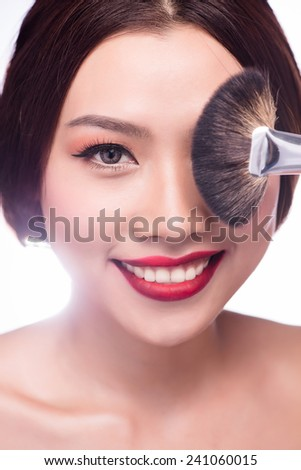 Portrait of young asian beautiful woman with brush for make-up. Professional Makeup for Brunette with Brown eyes - Red Lipstick, Smoky Eyes. Attractive Fashion Model Girl. Perfect Skin. Isolated - stock photo