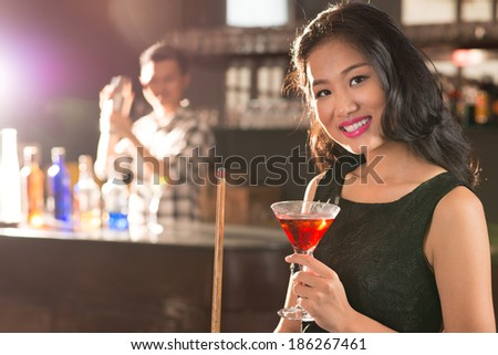 Portrait of young Asian brunette in the bar - stock photo