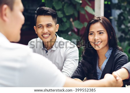 portrait of young asian business people meeting in a cafe and shake hand - stock photo