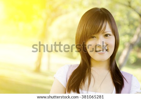 Portrait of young Asian college student standing on campus lawn, with backpack and smiling. - stock photo